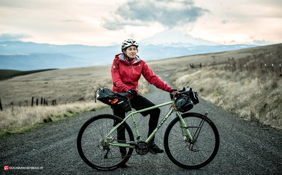 دوچرخه سوار توریست که دوچرخه تورینگ خود را در دست گرفته است