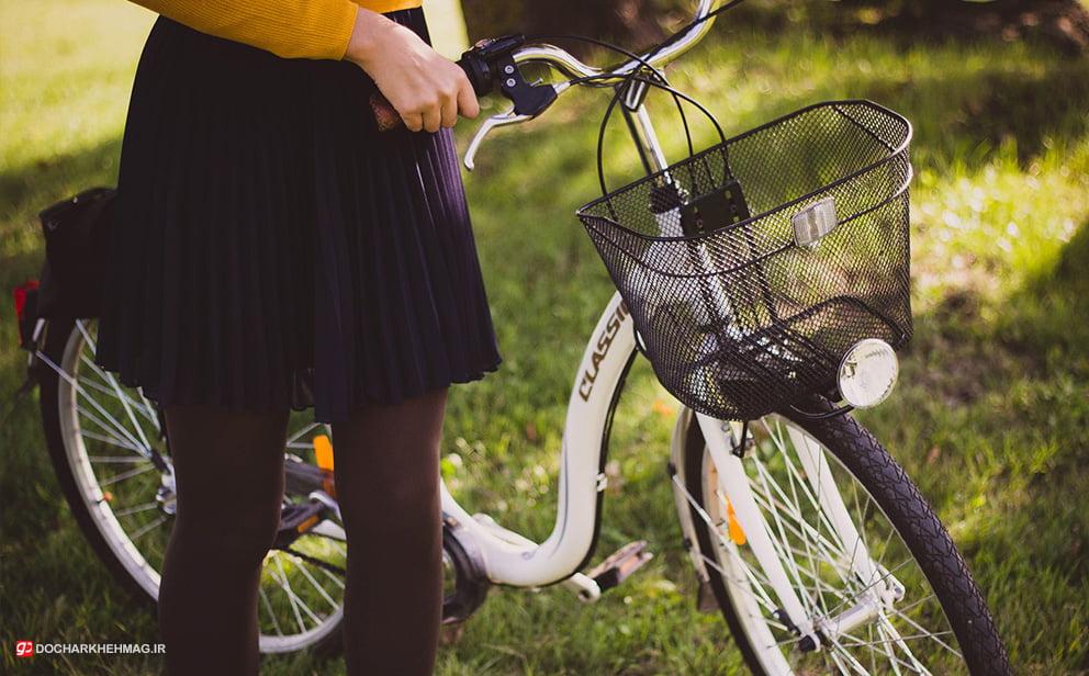 دوچرخه سوار خانم که دوچرخه را در دست گرفته است