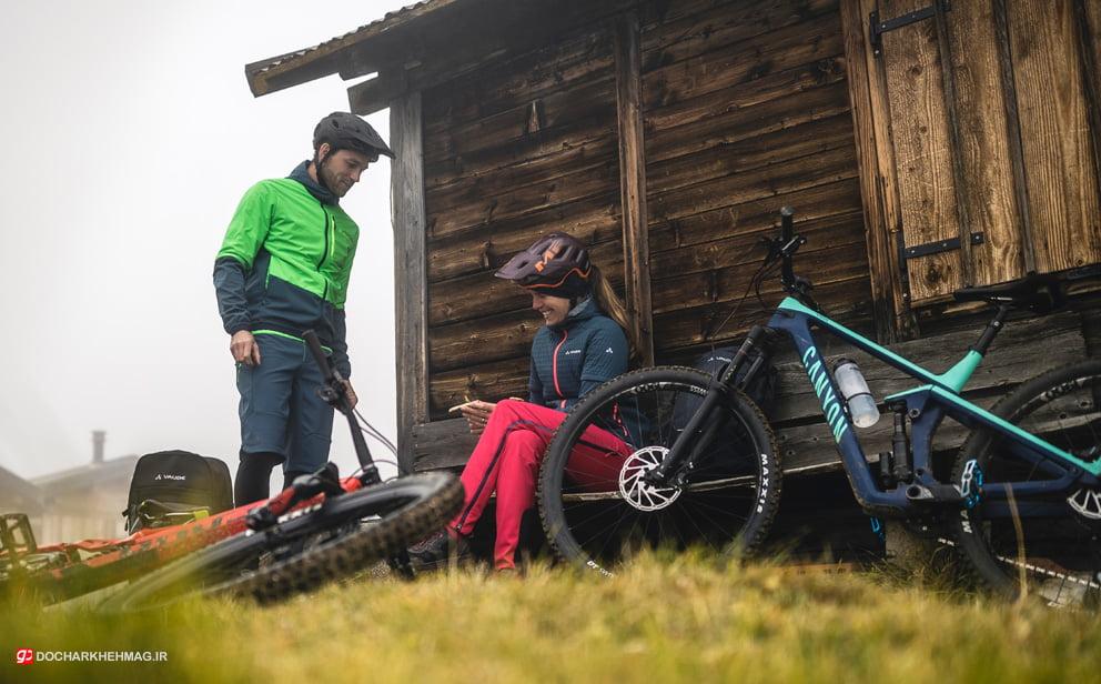 تصویر دو دوچرخه سوار کوهستان که در کنار دوچرخه خود استاده اند
