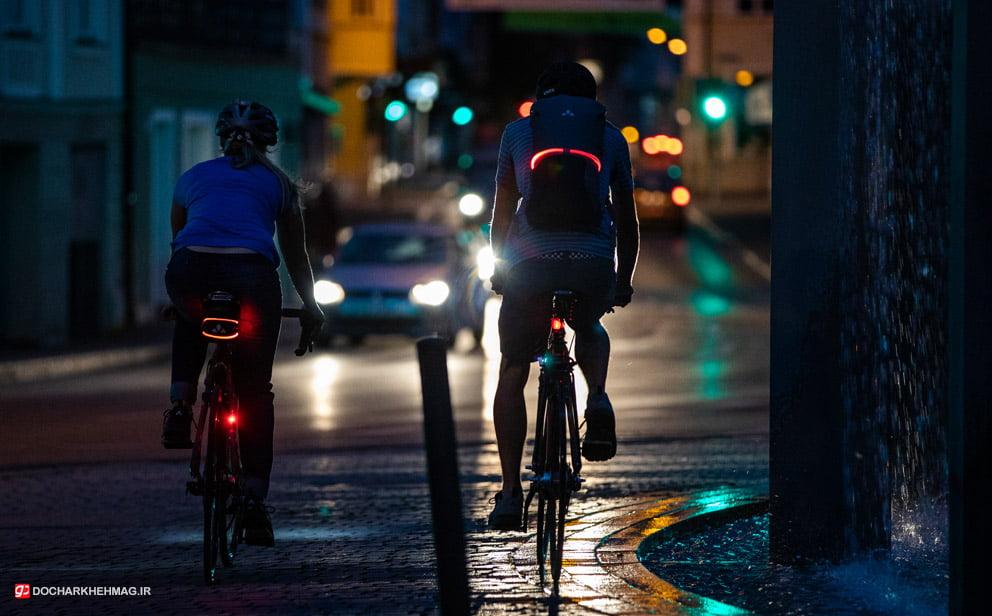 دو نفر در حال دوچرخه سواری در شب