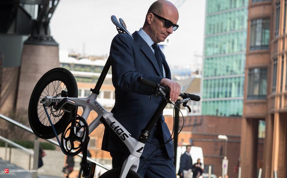 شخصی که دوچرخه تاشو را در بقل گرفته
