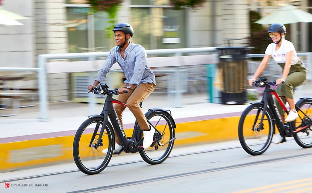 دو نفر در حال دوچرخه سواری با دوچرخه برقی